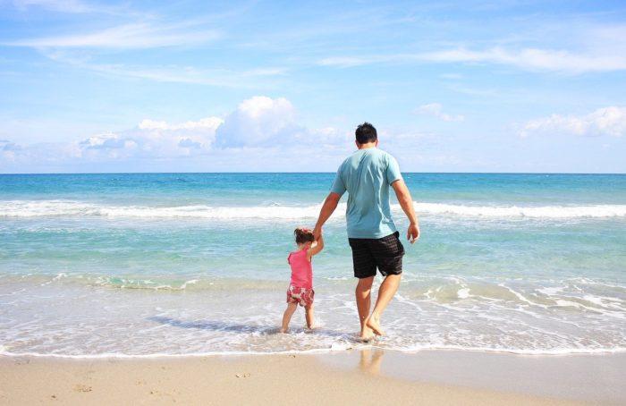 Feiertage - Brueckentage - Ferien -Mann mit Kind am Strand